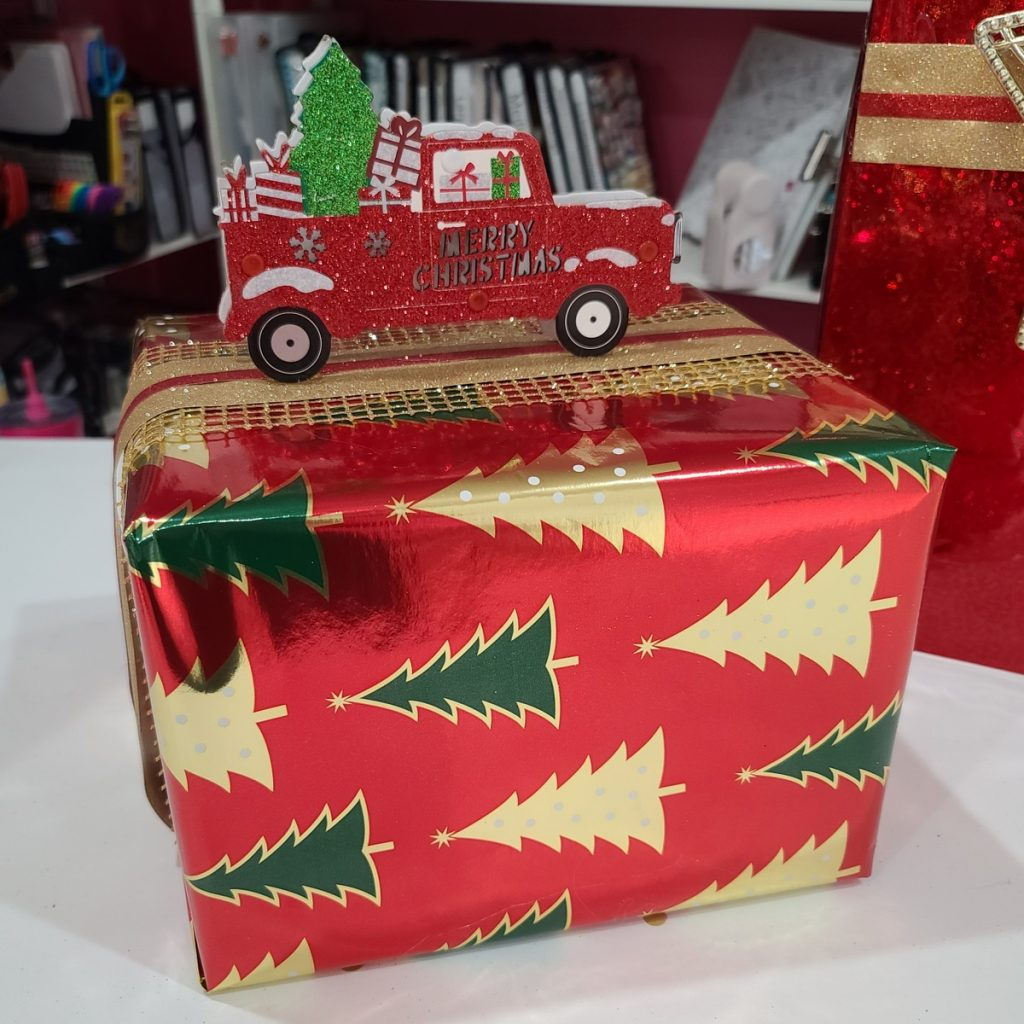 wrapped gift with red truck ornament on top
